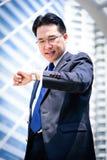 Ο ασιατικός επιχειρηματίας έχει το κράτημα μιας μαύρης τσάντας και το κοίταγμα στο ρολόι στη βιασύνη του χρόνου στοκ εικόνες