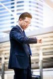 Ο ασιατικός επιχειρηματίας έχει το κράτημα μιας μαύρης τσάντας και το κοίταγμα στο ρολόι στη βιασύνη του χρόνου στοκ φωτογραφία