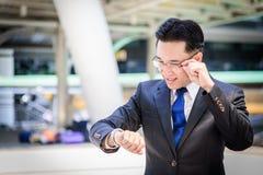 Ο ασιατικός επιχειρηματίας έχει το κράτημα μιας μαύρης τσάντας και το κοίταγμα στο ρολόι στη βιασύνη του χρόνου στοκ φωτογραφία με δικαίωμα ελεύθερης χρήσης