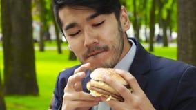 Ο ασιατικός επιχειρηματίας κάθεται στον πάγκο στο πάρκο και burger ρουθουνίσματος lunch φιλμ μικρού μήκους