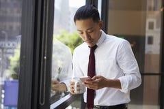 Ο ασιατικός επιχειρηματίας που χρησιμοποιεί το τηλέφωνο στο σύγχρονο γραφείο, κλείνει επάνω Στοκ Εικόνες