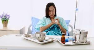 Ο ασιατικός θηλυκός ασθενής έχει το θωρακικό πόνο, καθορίζει στο υπομονετικό κρεβάτι, υπάρχει ιατρικός εξοπλισμός στον πίνακα, στ απόθεμα βίντεο
