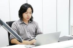 Ο ασιατικός μακρυμάλλης τύπος εστιάζει και συγκεντρώνεται στην εργασία του στο fron στοκ εικόνα