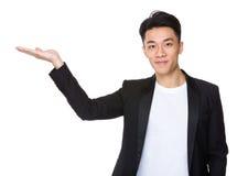 Ο ασιατικός νεαρός άνδρας με το χέρι παρουσιάζει με το κενό σημάδι Στοκ φωτογραφία με δικαίωμα ελεύθερης χρήσης