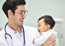 Ο ασιατικός παιδίατρος φροντίζει το μωρό Στοκ φωτογραφία με δικαίωμα ελεύθερης χρήσης