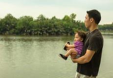 Ο ασιατικός πατέρας παίρνει το παιδί του για έναν περίπατο κατά μήκος της λίμνης που φέρνει το παιδί στα όπλα του στοκ εικόνα με δικαίωμα ελεύθερης χρήσης