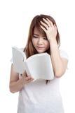 Ο ασιατικός πονοκέφαλος κοριτσιών δεν καταλαβαίνει ένα βιβλίο στοκ εικόνες