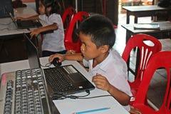 Ο ασιατικός σπουδαστής χρησιμοποιεί το πρόγραμμα υπολογιστών στοκ φωτογραφίες