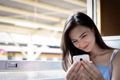 Ο ασιατικός ταξιδιώτης γυναικών έχει selfie με το τηλέφωνο μέσα στο τραίνο στο Χ στοκ εικόνες με δικαίωμα ελεύθερης χρήσης
