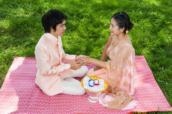 Ο ασιατικός ταϊλανδικός νεόνυμφος φορά το γαμήλιο δαχτυλίδι στη νύφη του στην ταϊλανδική τελετή Στοκ Φωτογραφίες