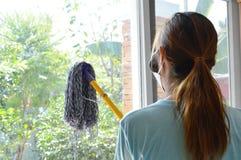 Ο ασιατικός χρησιμοποιημένος γυναίκα όχλος σκουπίζει την πόρτα γυαλιού στο σπίτι Στοκ Εικόνες