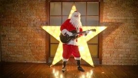 Ο αστέρας της ροκ Άγιου Βασίλη, τραγούδια Χριστουγέννων παιχνιδιών από την κιθάρα, έχει τη διασκέδαση, γιορτάζει τις διακοπές απόθεμα βίντεο