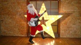Ο αστέρας της ροκ Άγιου Βασίλη, τραγούδια Χριστουγέννων παιχνιδιών από την κιθάρα, έχει τη διασκέδαση, γιορτάζει τις διακοπές φιλμ μικρού μήκους