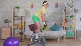 Ο αστείος ενεργός αθλητής από τη δεκαετία του '80 με ένα mustache δέσμευσε στο σπίτι σε ένα στάσιμο αργό MO ποδηλάτων απόθεμα βίντεο