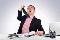 Ο αστείος επιχειρηματίας, κρέμασε έναν δεσμό στο γκρίζο υπόβαθρο Στοκ Φωτογραφίες