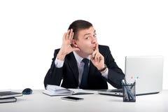 Ο αστείος επιχειρηματίας στο σκοτεινό κοστούμι κρυφακούει Στοκ Φωτογραφία