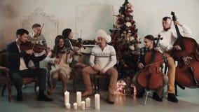 Ο αστείος μουσικός στο άσπρο καπέλο γουνών ανοίγει τη κάμερα, η σειρά quintet αρχίζει απόθεμα βίντεο