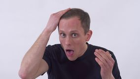 Ο αστείος νεαρός άνδρας κάνει το παράξενο πρόσωπο και ισιώνει την τρίχα στο κεφάλι με ένα χέρι Βλάστηση σε μια άσπρη ανασκόπηση φιλμ μικρού μήκους