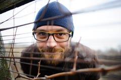 Ο αστείος νεαρός άνδρας με τα γυαλιά και μια γενειάδα κοιτάζει έξω από πίσω από το φράκτη Στοκ Εικόνες