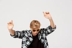 Ο αστείος ξανθός όμορφος νεαρός άνδρας που φορά τα γυαλιά ηλίου και τον περιστασιακό χορό πουκάμισων καρό που κυματίζουν δίνει το Στοκ Φωτογραφία