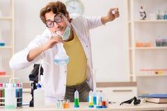 Ο αστείος τρελλός φαρμακοποιός που κάνει τα πειράματα και τις δοκιμές στοκ φωτογραφία