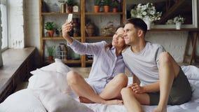 Ο αστείος φίλος και η φίλη νέων παίρνουν selfie με τα ανόητα πρόσωπα που έχουν τη διασκέδαση και που φιλούν καθμένος επάνω απόθεμα βίντεο