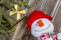 Ο αστείος χιονάνθρωπος στο κόκκινο καπέλο με το κιβώτιο δώρων και οι ερυθρελάτες διακλαδίζονται στο συμπαθητικό ξύλινο υπόβαθρο Στοκ φωτογραφία με δικαίωμα ελεύθερης χρήσης