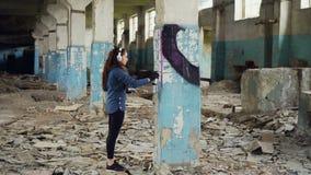 Ο αστικός καλλιτέχνης διακοσμεί τη στήλη στην εγκαταλειμμένη αποθήκη εμπορευμάτων με την αφηρημένη εικόνα χρησιμοποιώντας το χρώμ φιλμ μικρού μήκους
