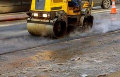 Ο αστικός δρόμος είναι κάτω από την κατασκευή, ασφαλτόστρωση του κίτρινου κυλίνδρου Στοκ Φωτογραφία