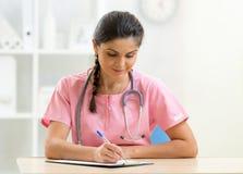Ο λατρευτός γιατρός γυναικών γράφει τη συνεδρίαση στον πίνακα στο γραφείο Στοκ Εικόνες