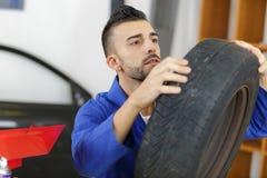 Ο αυτόματος μηχανικός επιλέγει τη ρόδα για το αυτοκίνητο στο κατάστημα ροδών Στοκ φωτογραφία με δικαίωμα ελεύθερης χρήσης