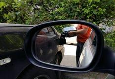 Ο αυτόματος μηχανικός χύνει τη βενζίνη από το μεταλλικό κουτί στη μηχανή στοκ φωτογραφίες