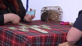 Ο αφηγητής τύχης προβλέπει στο μέλλον γυναικών με τις κάρτες tarot στον άξονα 4K απόθεμα βίντεο
