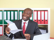 Ο αφρικανικός επιχειρηματίας στο γραφείο είναι ευχαριστημένος από καλό  Στοκ φωτογραφία με δικαίωμα ελεύθερης χρήσης