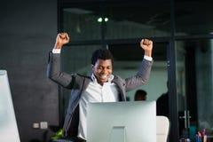 Ο αφρικανικός επιχειρηματίας στο γραφείο, χειρονομία επιτυχίας, στόχος έφθασε, ευτυχές άτομο Στοκ Φωτογραφία