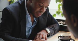 Ο αφρικανικός επιχειρηματίας υπογράφει μια σύμβαση σε έναν καφέ απόθεμα βίντεο