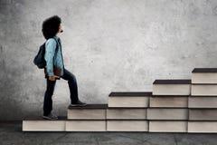 Ο αφρικανικός σπουδαστής αναρριχείται διαμορφωμένα στα σκαλοπάτι βιβλία Στοκ Φωτογραφίες