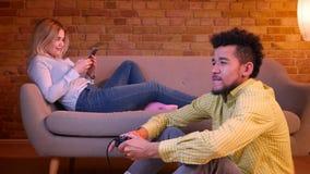 Ο αφρικανικός τύπος κάθεται videogame παιχνιδιού πατωμάτων με το πηδάλιο και τις καυκάσιες εργασίες κοριτσιών με το smartphone στ απόθεμα βίντεο