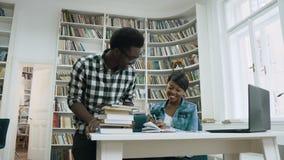 Ο αφρικανικός τύπος που περπατά στη βιβλιοθήκη, που δίνει πέντε στο ελκυστικό αφρικανικό κορίτσι και αρχίζει μαζί στη βιβλιοθήκη απόθεμα βίντεο