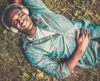 Ο αφροαμερικάνος ακούει μουσική σε ένα πάρκο Στοκ Εικόνες