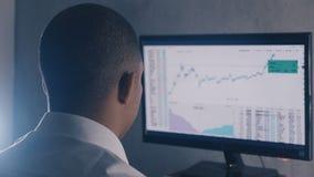 Ο αφροαμερικανός επιχειρηματίας στο άσπρο πουκάμισο αναλύει την αγορά πωλήσεων Η πίσω άποψη του χρηματιστή λειτουργεί με οικονομι φιλμ μικρού μήκους