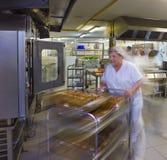 Ο αχθοφόρος κουζινών ωθεί ένα καροτσάκι των ζυμών στοκ εικόνα