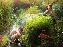 Ο αδελφός και η αδελφή αμφιθαλών εφήβων ψεκάζουν ο ένας τον άλλον με τη μάνικα νερού στοκ φωτογραφία