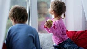 Ο αδελφός και η αδελφή κάθονται στη στρωματοειδή φλέβα παραθύρων, που τρώει τα μήλα και που φαίνεται έξω παράθυρο φιλμ μικρού μήκους