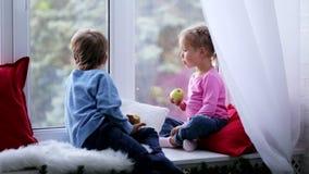 Ο αδελφός και η αδελφή κάθονται στη στρωματοειδή φλέβα παραθύρων, που τρώει τα μήλα και που φαίνεται έξω παράθυρο απόθεμα βίντεο