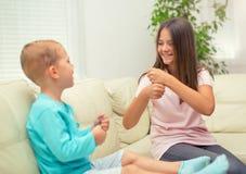 Ο αδελφός και η αδελφή μαθαίνουν τη γλώσσα σημαδιών στο σπίτι Στοκ εικόνα με δικαίωμα ελεύθερης χρήσης