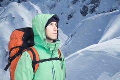 Ο αλπινιστής ατόμων ανατρέχει ενάντια σε ένα τοπίο χειμερινών βουνών Στοκ Φωτογραφίες