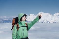Ο αλπινιστής ατόμων ανατρέχει ενάντια σε ένα τοπίο χειμερινών βουνών Στοκ Φωτογραφία