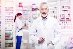 Ο βέβαιος γκρίζος-μαλλιαρός φαρμακοποιός που κρατά δικούς του παραδίδει την τσέπη στοκ φωτογραφία με δικαίωμα ελεύθερης χρήσης