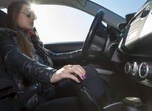 Ο βέβαιος θηλυκός δρομέας οδηγεί το αυτοκίνητο στοκ εικόνες